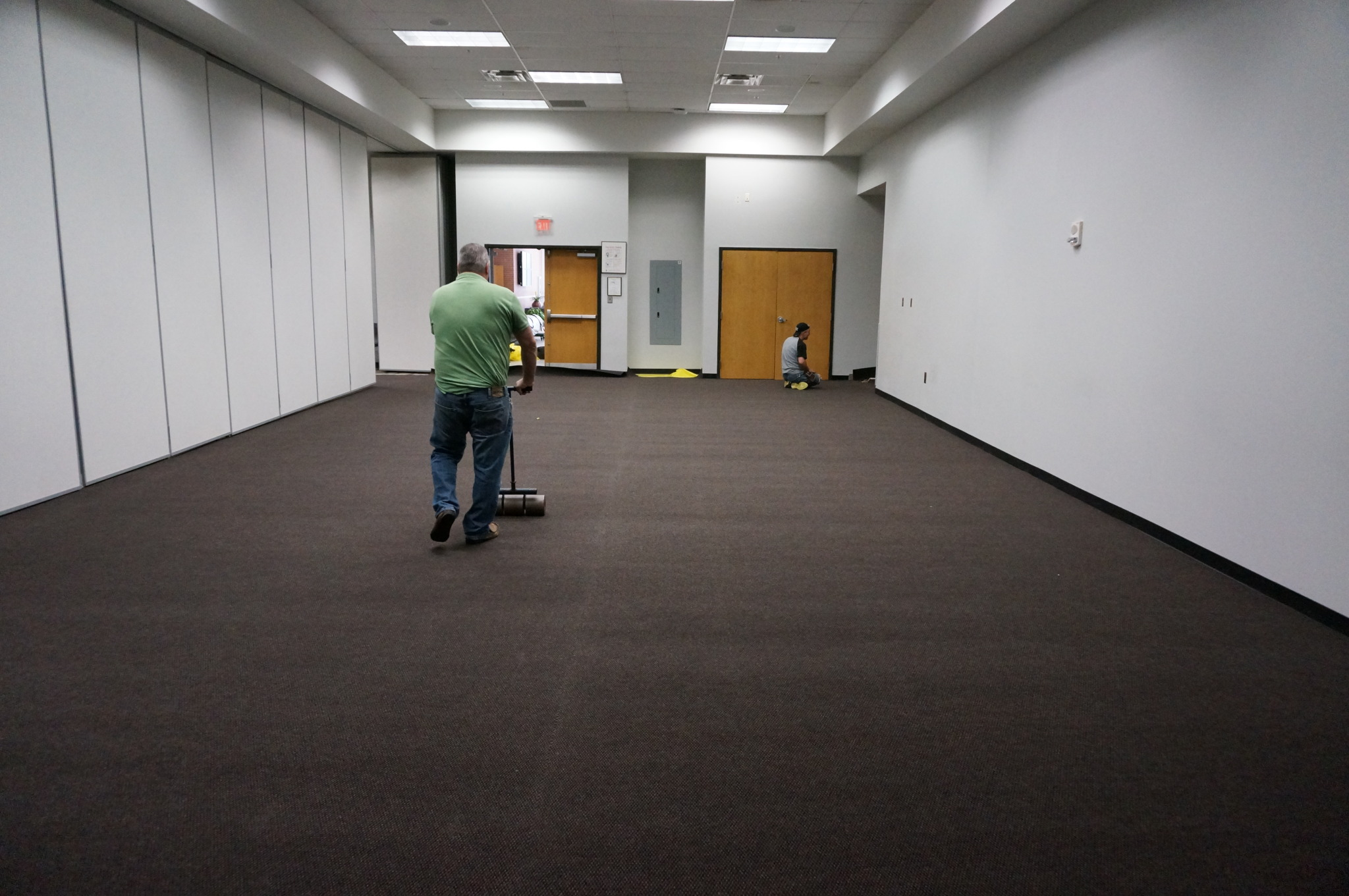 The carpet is being secured to the floor with a roller.